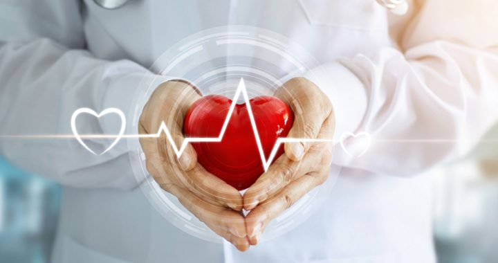 a doctor's hands hold a red heart
