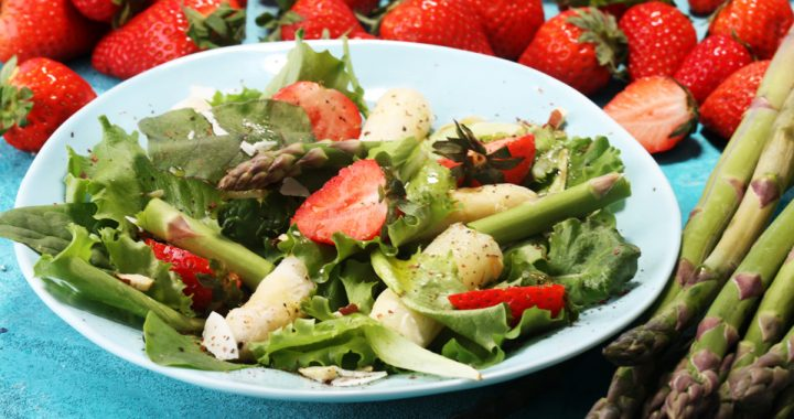 A salad with spring vegetables and fruits such as strawberries and asparagus on a white plate sits on a table