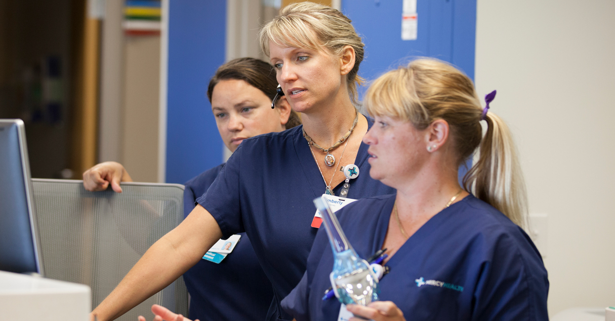 Mercy Health Nurses wearing dark blue scrubs gather around a monitor at the hospital