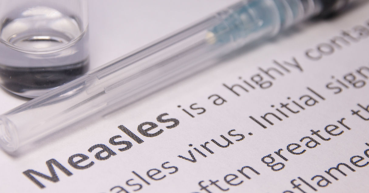 A measles vaccine lays on a sheet of paper with the definition of the measles virus.