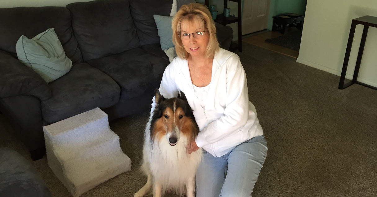 Rebecca, a trigeminal neuralgia patient, poses with her brown and white dog