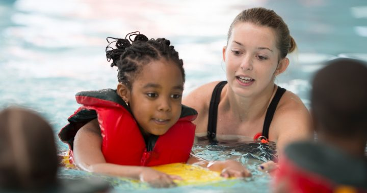 a girl in a red life jacket swims along side a female swimming instructor