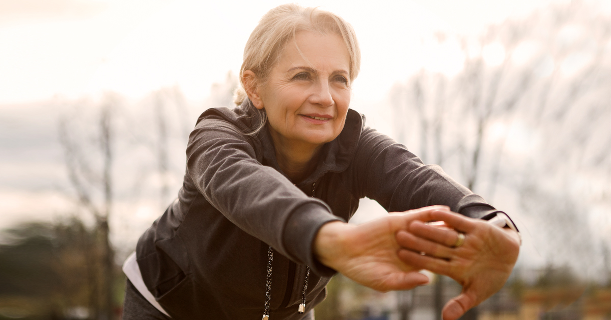 Woman practicing stretching exercises outside.
