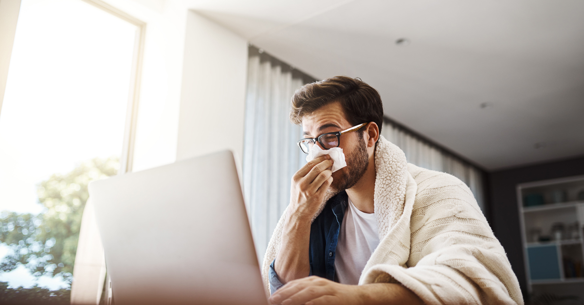 Man wiping his noes while looking at computer.