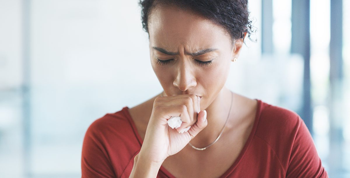 Woman experiencing a cough, one of the COVID-19 symptoms.