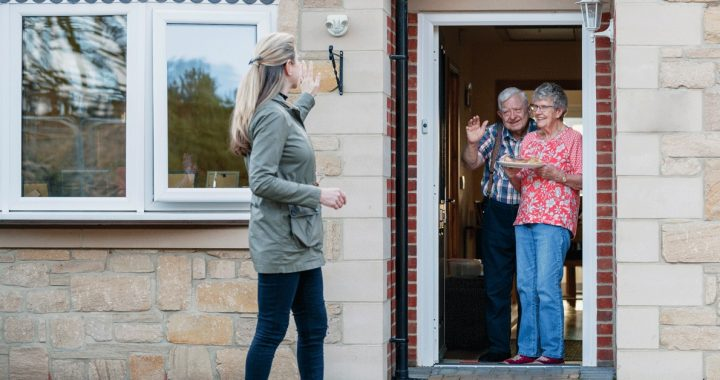 Woman waving to loved ones from outside their home during COVID-19.