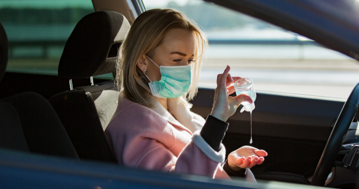 Woman using hand sanitizer in her care while wearing a face covering.
