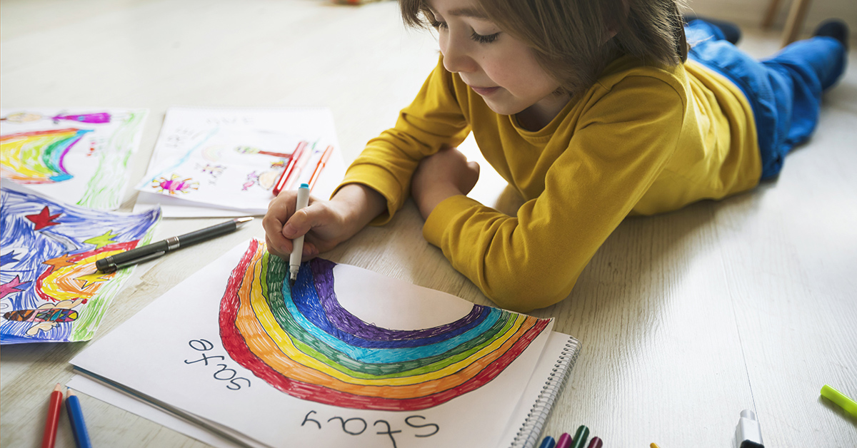 Child coloring a rainbow picture to help spread messages of hope during COVID-19.