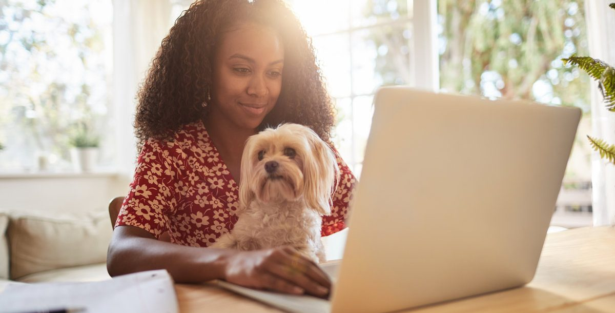 Woman working from home during COVID-19 with her dog on her lap.