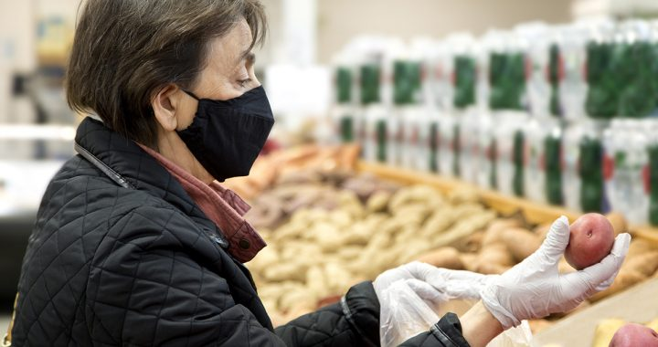 A woman at the grocery store wearing latex gloves during COVID-19.