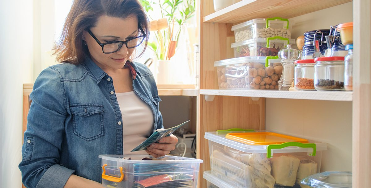 Woman looking through pantry for recipe ingredients during COVID-19.