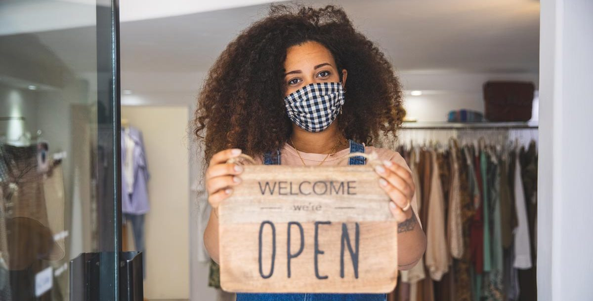 """A woman holding a """"we are open"""" sign in front of her store while wearing a face mask."""