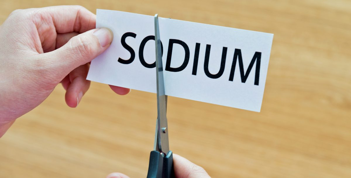 "Scissors cutting the word ""sodium"" on a piece of paper."