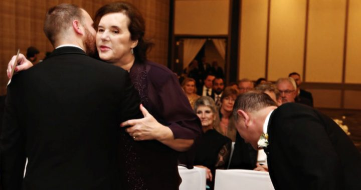 Sharon and Josh embracing at his wedding ceremony.