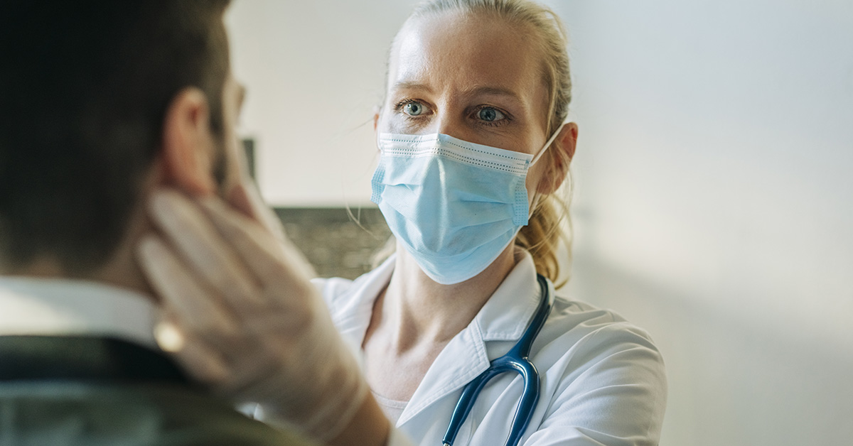 A medical provider taking care of a patient with a face mask on.
