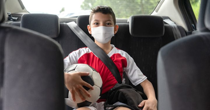 A boy going to his soccer game wearing a face mask during COVID-19.