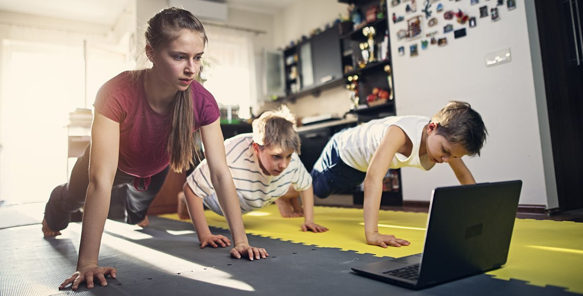 Three children practicing strength training exercises together at home.
