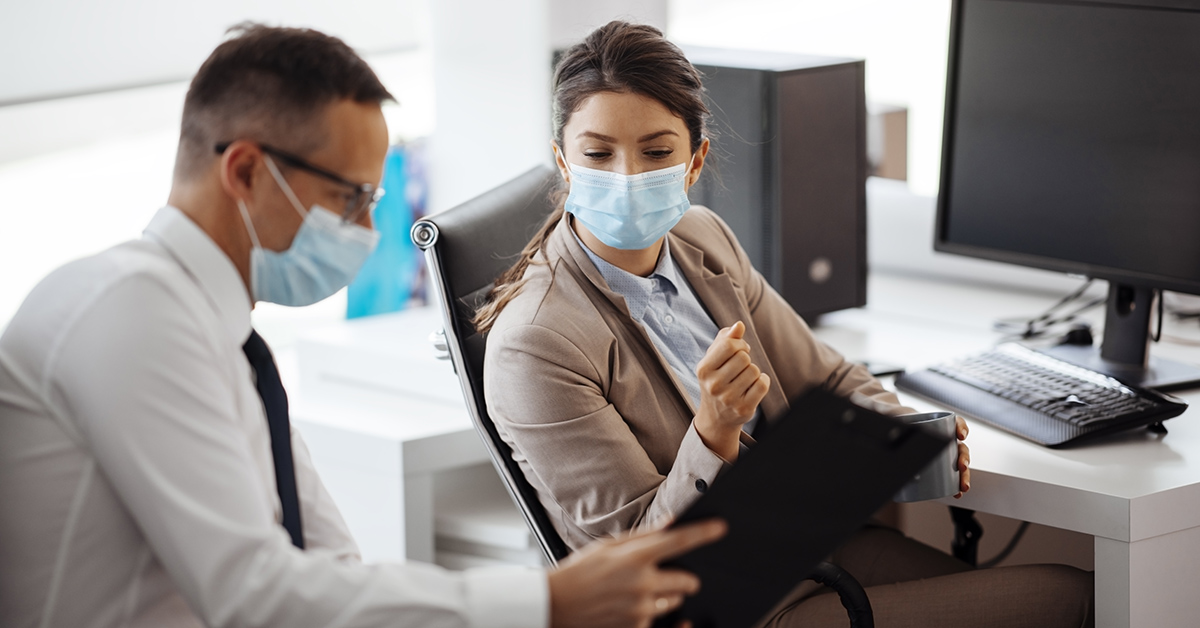Two coworkers reviewing data together while wearing face masks.