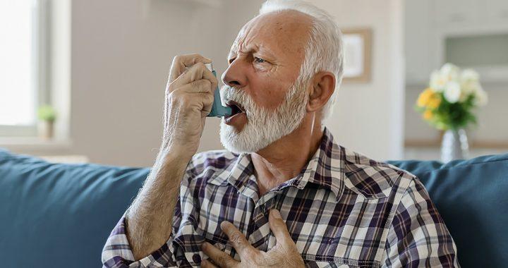 A man suffering from asthma using an inhaler.