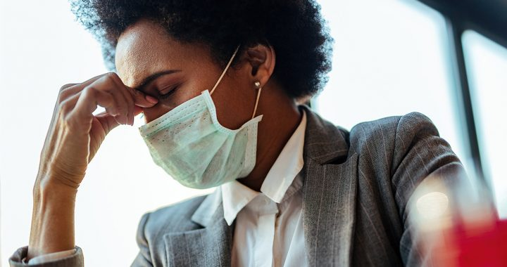 A woman experiencing a headache while wearing a face mask.