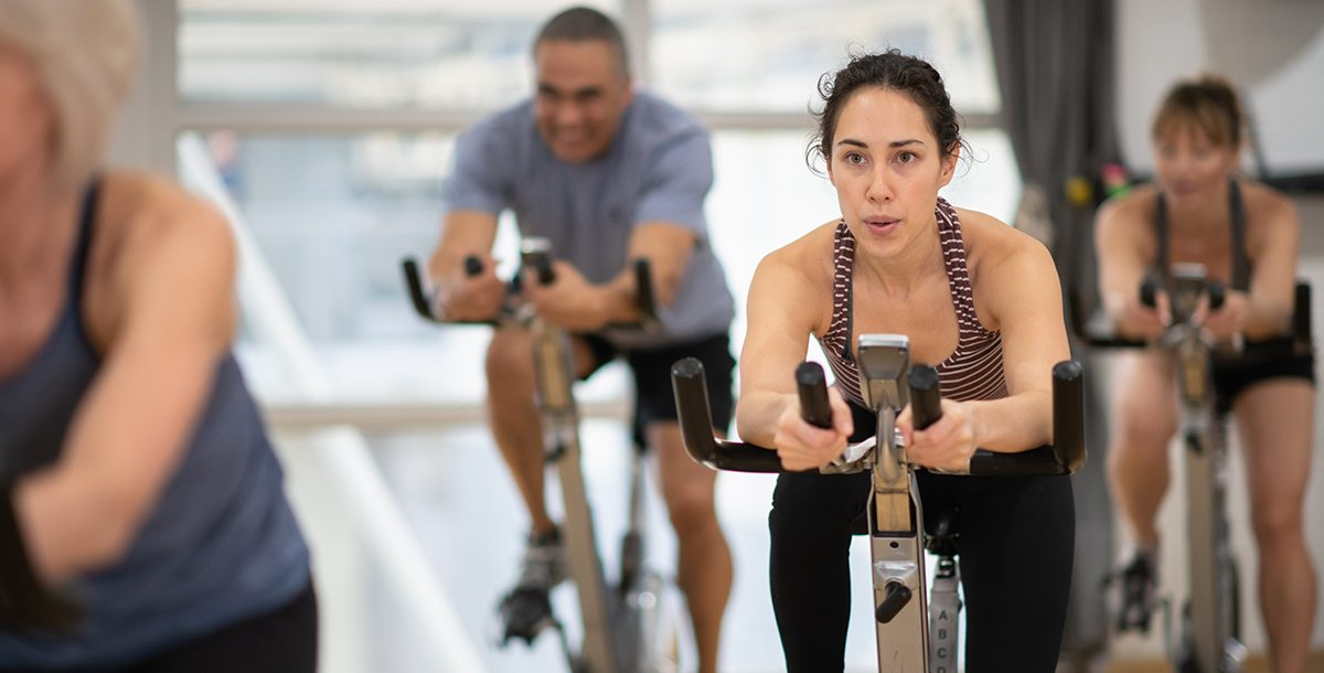 A woman participating in a cycle class at the gym during COVID-19.