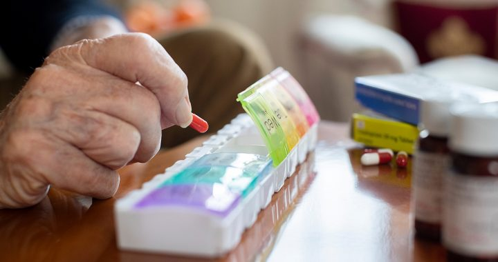 Someone using a pill organizer to manage their medications during COVID-19.