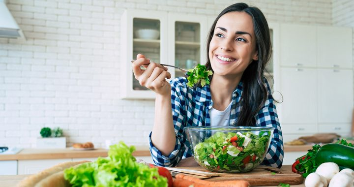 A woman enjoying a salad as part of her plant-based diet.