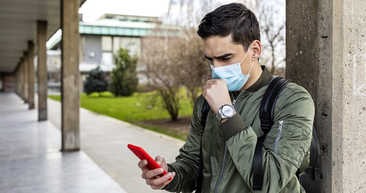A man getting a contact tracing alert on his smartphone.