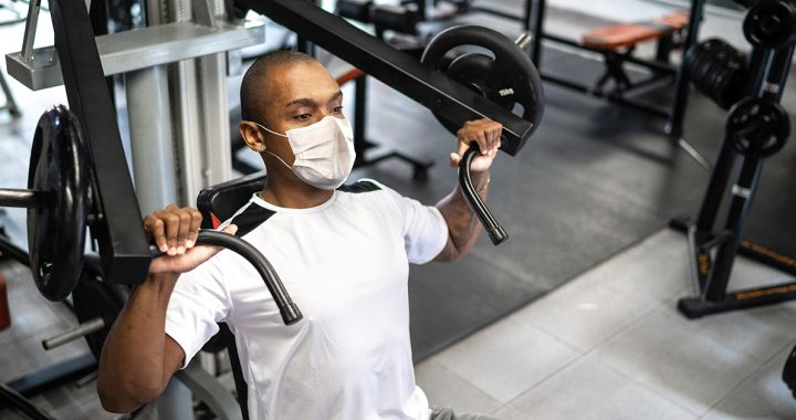 A man exercising at the gym while wearing a face mask during COVID-19.