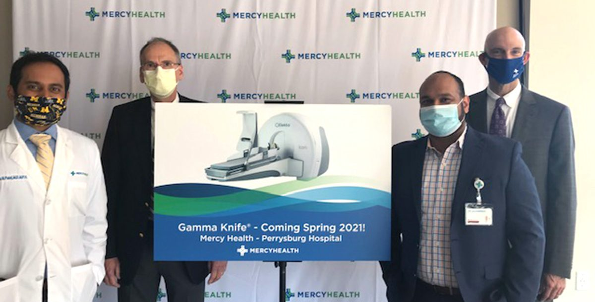 Mercy Health Perrysburg Hospital leadership team members stand surrounding a poster depicting a gamma knife machine