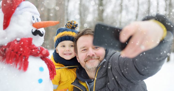 A father and son participating in a virtual snowman decorating contest.