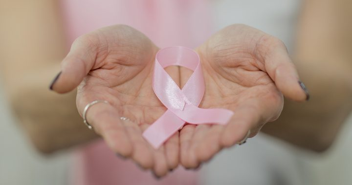 A woman holding a breast cancer ribbon.