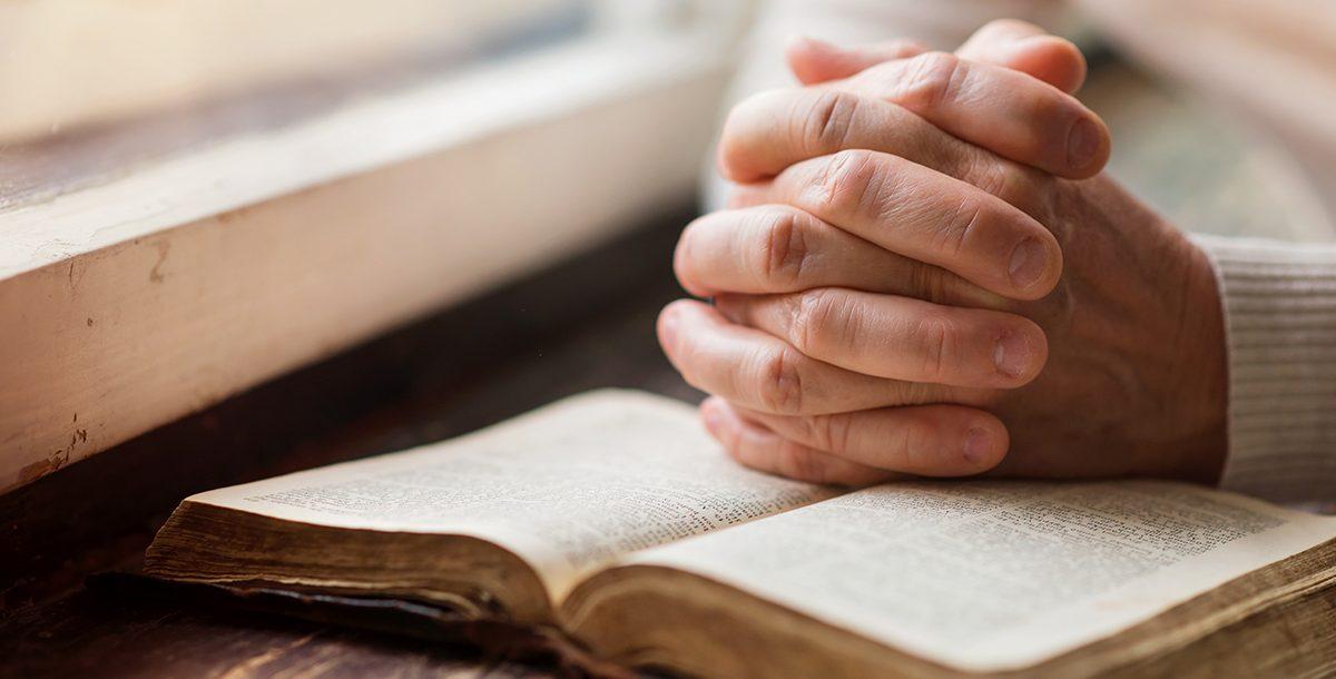 A person praying using a bible.