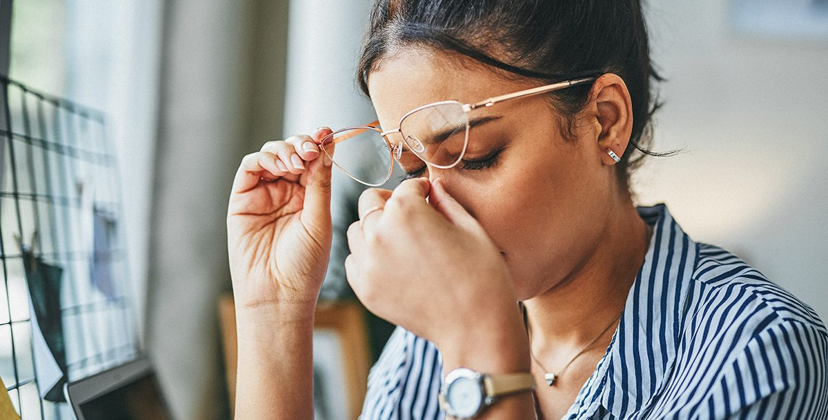 A women touching her face while stressed.
