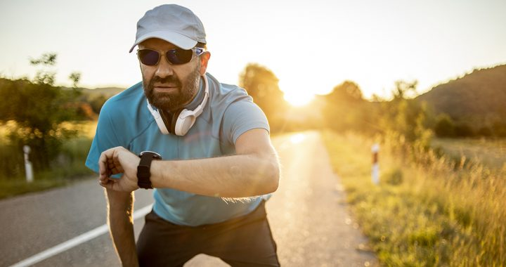 A man wearing sunglasses and a hat while running outside.