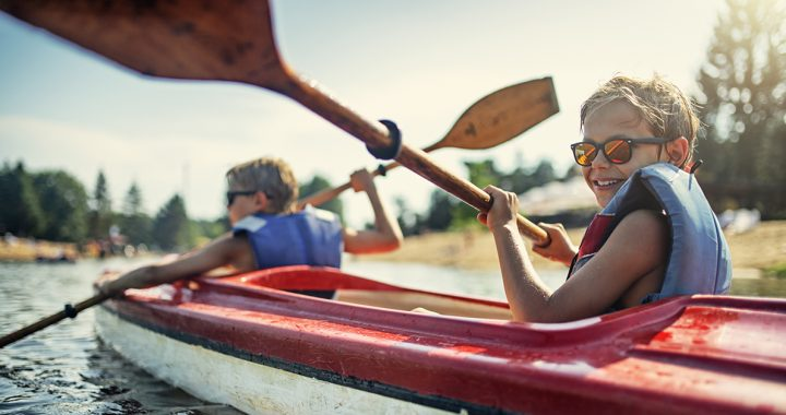 A child kayaking with their parent.
