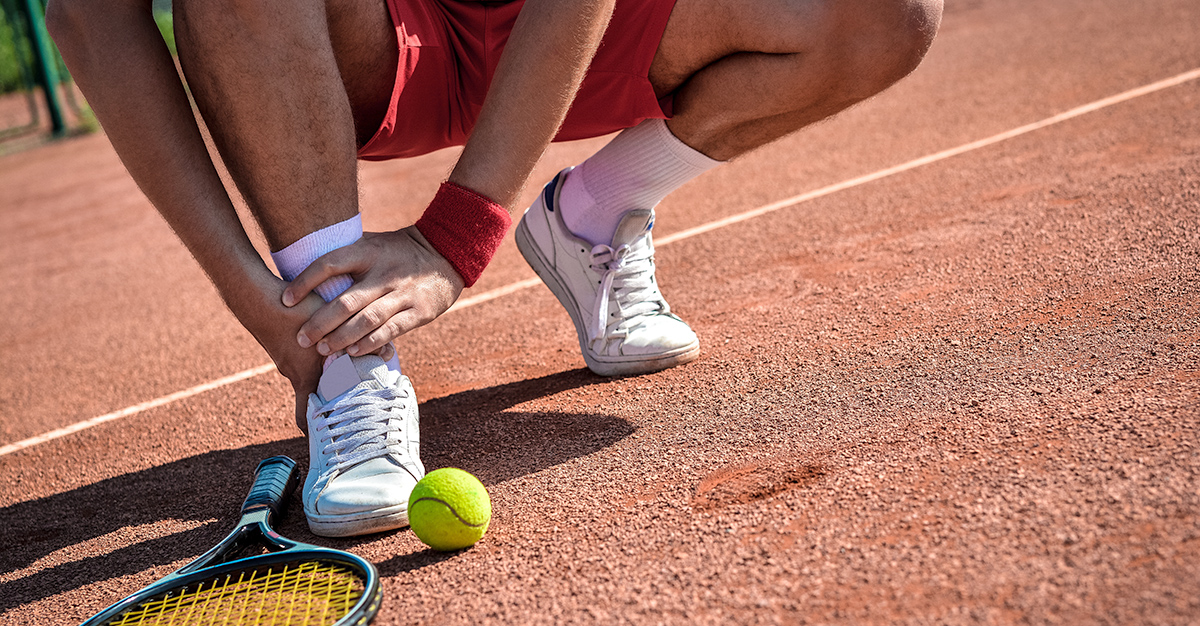 A person experiencing an ankle injury while playing tennis.