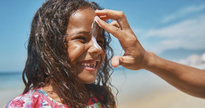 A child putting sunscreen on.