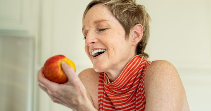 A woman eating an apple.