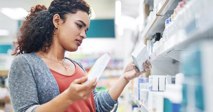 A woman looking at different medications at the pharmacy.