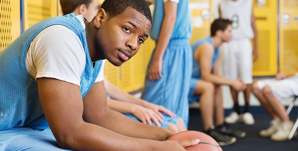 A high school athlete sitting in a locker room.