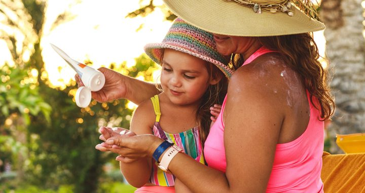 A mother putting sunscreen on her daughter.