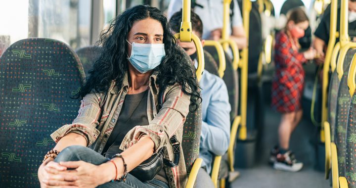 A woman wearing a face mask on public transportation.