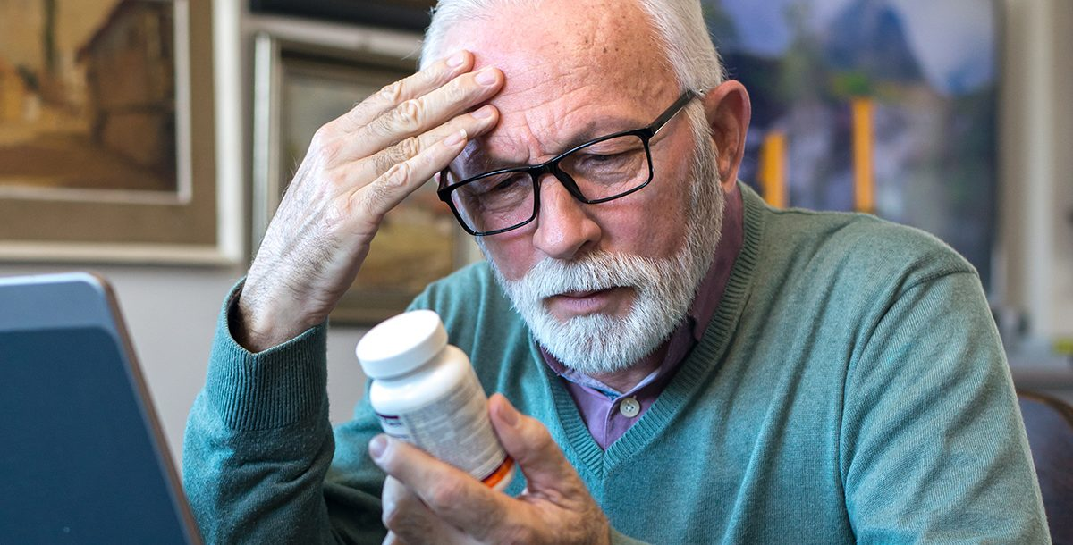 A man looking at a medication bottle.
