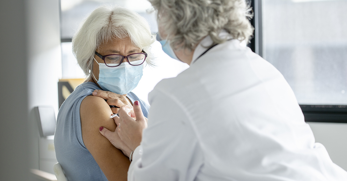 A woman getting her flu and COVID-19 vaccines.